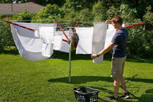 Load image into Gallery viewer, A young man hanging out clothes on a sunny day on his Sunshine Clothesline.