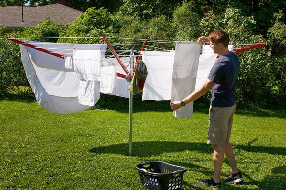 A young man hanging out clothes on a sunny day on his Sunshine Clothesline.