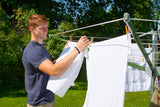 A man hanging clothes on a Deluxe DS9 Sunshine Clothesline