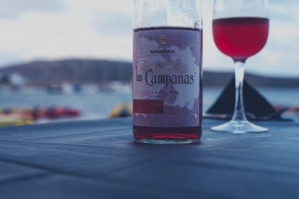A wine bottle in from of a blurry sea-side backdrop