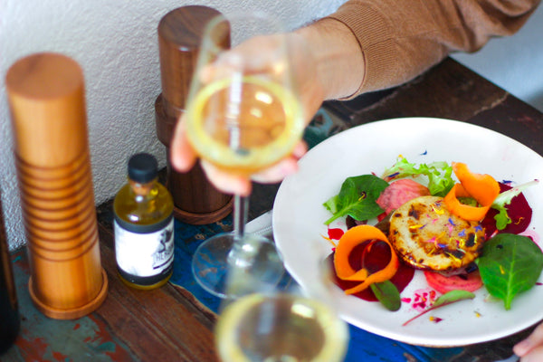 A glass of white wine with a beautiful minimalist salad