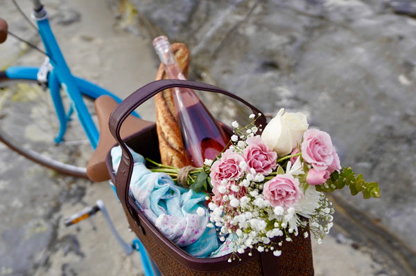 A bike basket with a bottle of wine and a bouquet of flowers inside