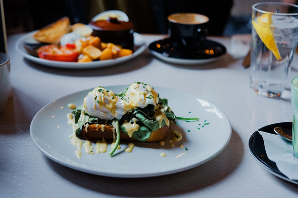 Perfectly crafted eggs benedict on a bright white table