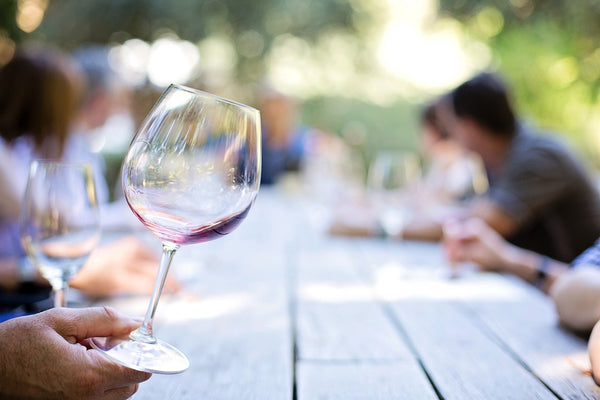 A wine glass being swirled at a picnic table outdoors