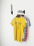Assorted clothes being hung on a white wall with COSTA by Wallniture.