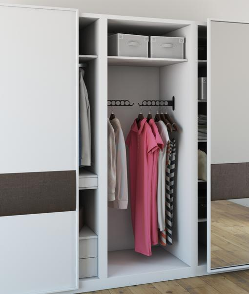 Assorted clothes being hung inside a minimalist closet with COSTA by Wallniture.