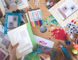 Painting a natural wooden CRAFT picture frame by Wallniture green on a table; arts and crafts, pens, markers, scissors.
