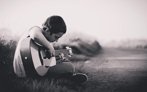 Image of boy playing the guitar.
