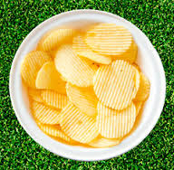 fake grass with bowl of potato chips