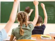 girl with hand raised in school