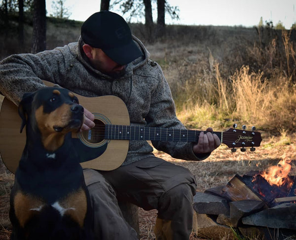 WeatherWool Advisor Greg Schauble @Scablands_Bushcraft and his guitar in his WeatherWool Anorak in Lynx Pattern