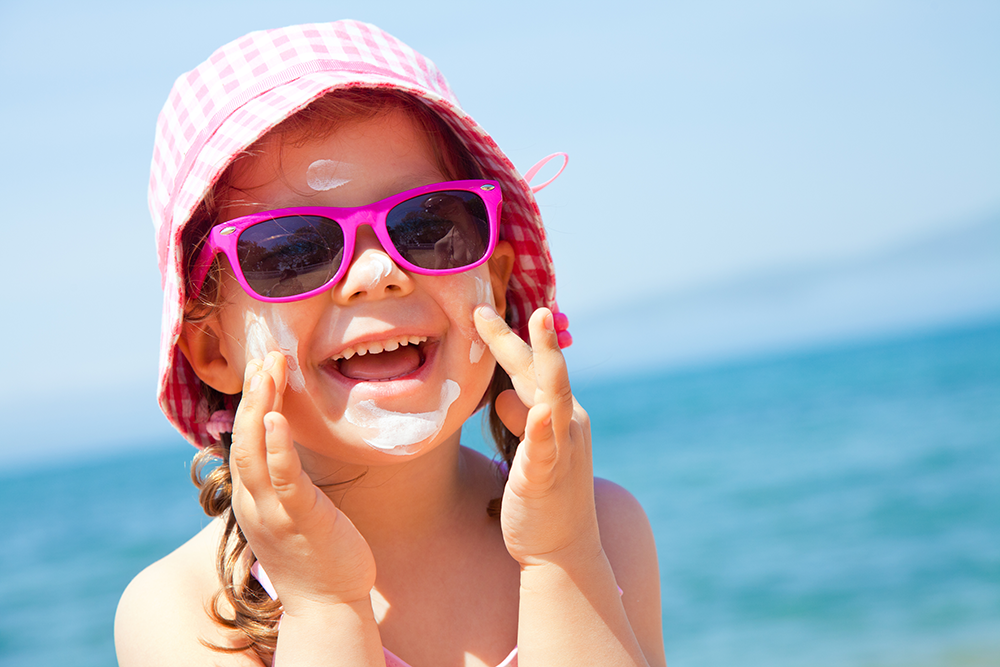 girl with pink sunglasses putting on sunscreen