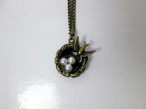 small mama bird necklace with three bird eggs in nest
