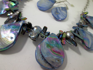 closeup view of rainbow blue seashell and pearl necklace and earrings set