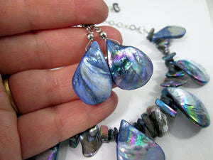 closeup view of rainbow blue seashell earrings