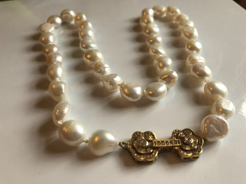 Necklace: Large baroque ivory pearl necklace with a goldtone flower clasp classic