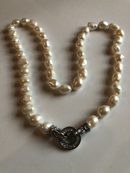 Medium  ivory pearl necklace with a baguette encrusted round clasp classic