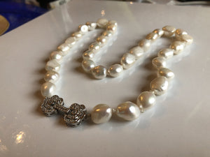Necklace: Large baroque ivory pearl necklace with a silvertone flower clasp classic