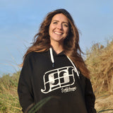 'Surf Kernow Logo' - Black organic cotton hoodie – Modelled by local surfer Dannie at Fistral beach in Newquay, Cornwall.