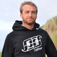 'Surf Kernow Logo' - Black organic cotton hoodie – Modelled by local surfer JB at Fistral beach in Newquay, Cornwall.