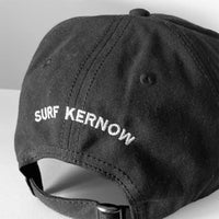 Back shot of our black organic Cotton Baseball Cap with embroidered 'Surf Kernow' text above the adjustable strap and buckle – designed and embroidered in Cornwall.