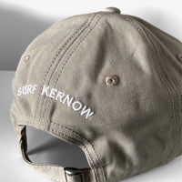 Back shot of our stone-coloured organic Cotton Baseball Cap with embroidered 'Surf Kernow' text above the adjustable strap and buckle – designed and embroidered in Cornwall.
