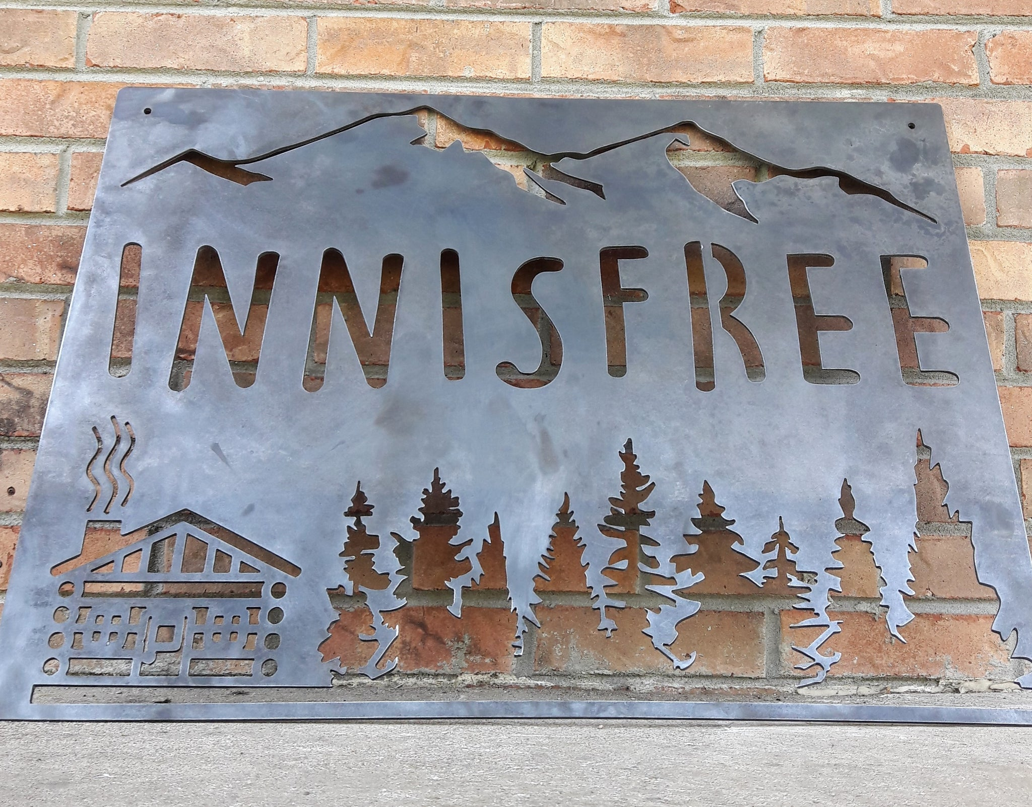 "This sign is displays a mountain range in the background with a forest and cabin. The sign reads, ""INNISFREE""."