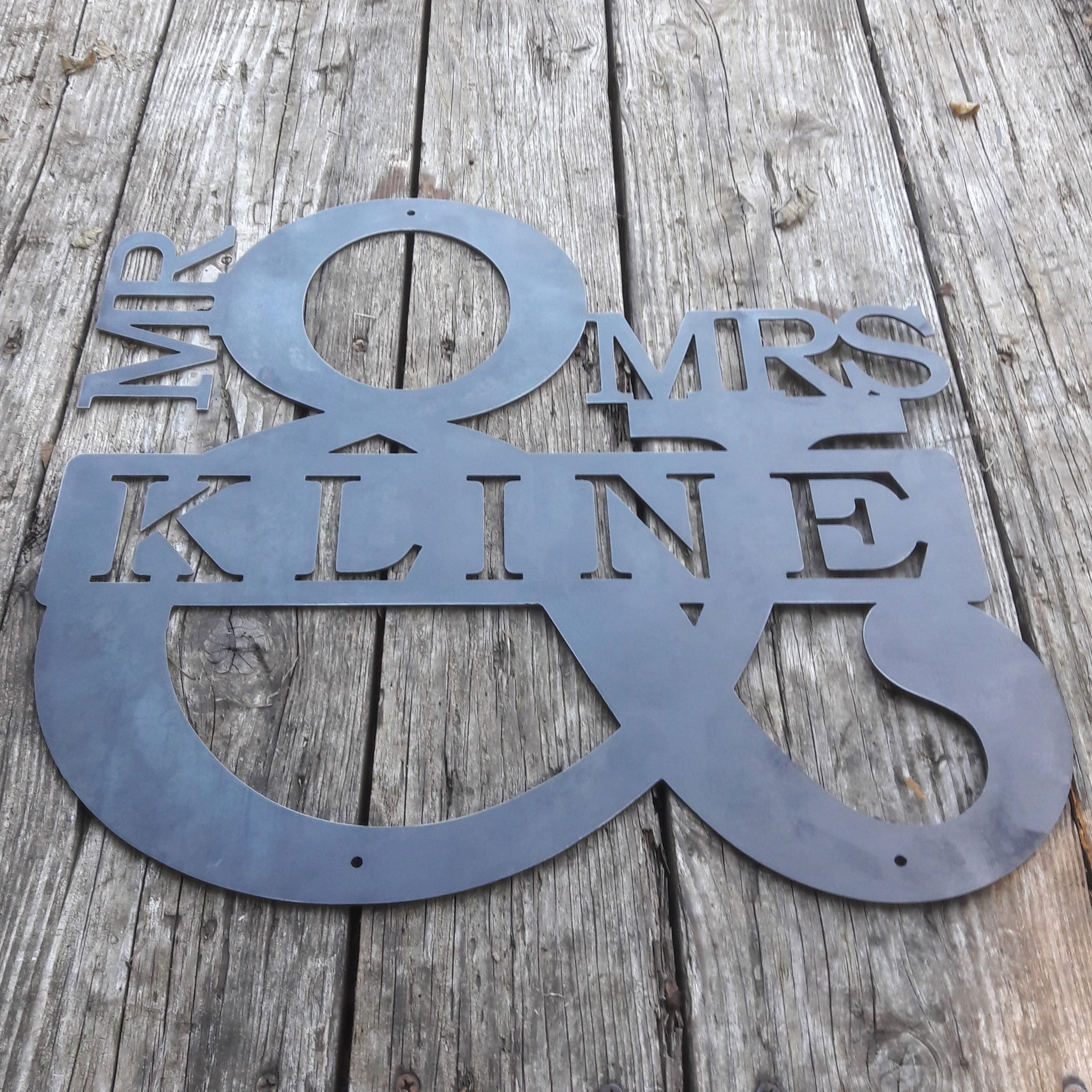 "Personalized metal sign in the shape of an ampersand. The sign reads, ""Mr. & Mrs. Kline""."