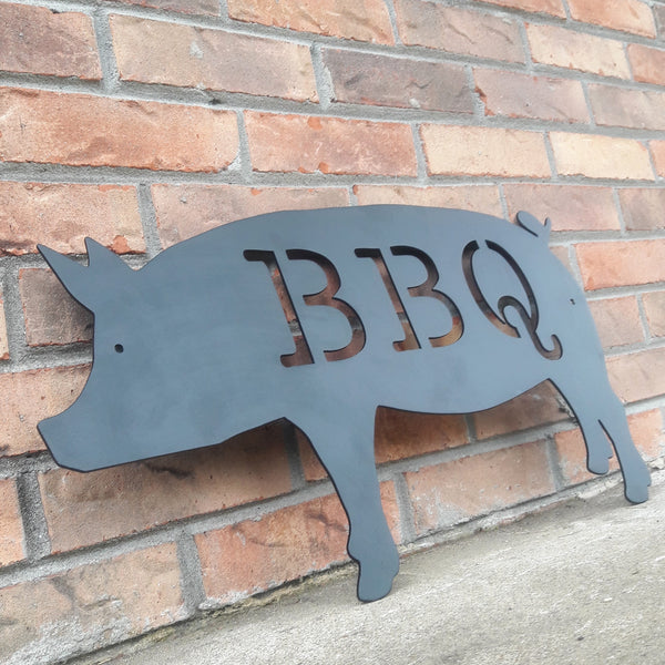 "This is a black powder coated metal sign in the shape of pig with two 1/4"" mounting holes. The sig reads, ""BBQ"""