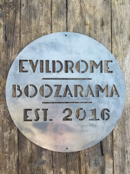 "This is a round art deco sign that has three lines of text with a straight line seperating them. The sign reads, ""Evildrome Boozarama Est. 2016"""