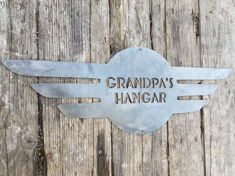 "This is a round metal sign with wings. It looks like a pilot's pedant. the sign reads, ""Grandpa's Hangar"""
