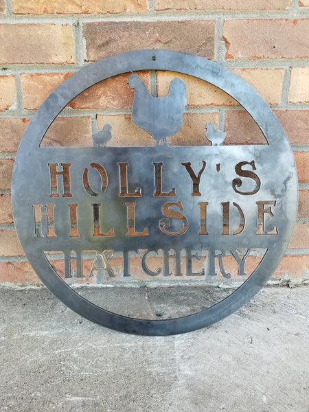 "This metal sign is personalized and has the image of a chicken and two chicks at the top. The sign reads, ""Holly's Hillside Hatchery""."