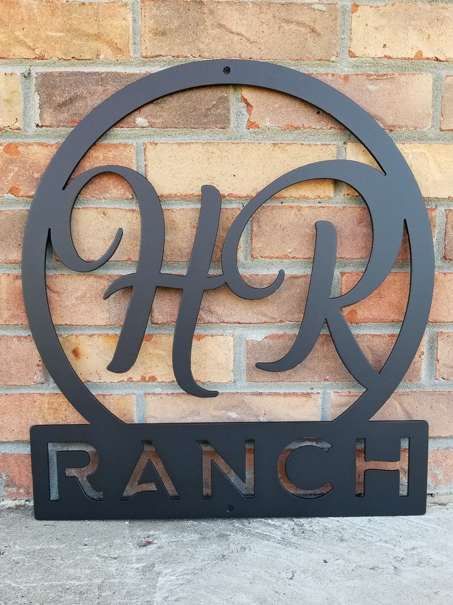 "Round metal monogram with two letters at the top and a line of text at the bottom. The sign reads, "" HR Ranch"". The sign is powder coated black."