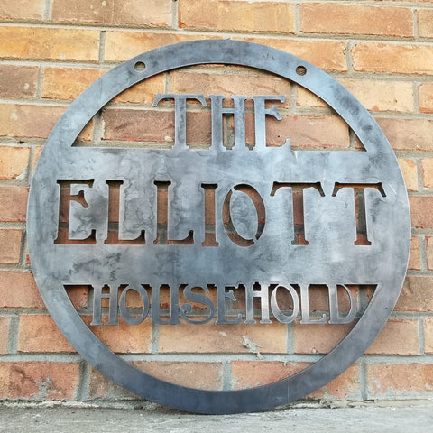 "This is a round metal sign with 1/2"" mounting holes that reads, "" The Elliot Household"""