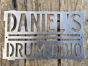 "This is a rectangular sign that reads, ""Daniel's Drum Dojo""."