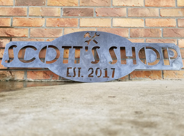 "This is a raw steel, custom metal sign.  At the top of the sign is an image of tools. There is two lines of text on this sign which reads, ""Scott's Shop, Est. 2013"""