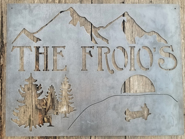 "This is rectangular sign that displays a mountain range over a lake that is surrounded by trees. In the center of the lake is a boat with the figure of a man fishing who cast a shadow by the light of a sunset. Under the mountain range is a line of text that reads, ""The Froio's"""