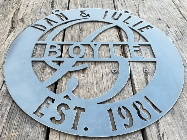 "This is a round metal monogram with 1/2"" dog ears for hanging that reads, "" Dan & Julie, Boyle, Established 1981"""