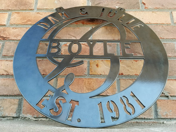 "This is a round outdoor clear powder coated monogram with 1/2"" dog ears for hanging that reads, "" Dan & Julie, Boyle, Established 1981"""