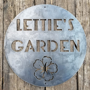 "This is a round sign with an image of a flower below two lines of text which read, ""Lettie's Garden""."