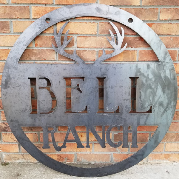 "Round metal sign with an image of antlers at the top and two lines of text which read, ""Bell Ranch"""