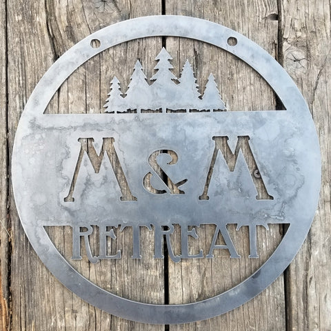"This custom metal sign has a cluster of trees at the top and reads, ""M&M Retreat"""