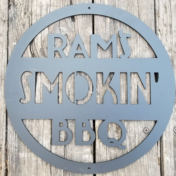 "This is a round art deco. sign that has three lines of text. The sign reads, "" Rams Smokin' BBQ"""""