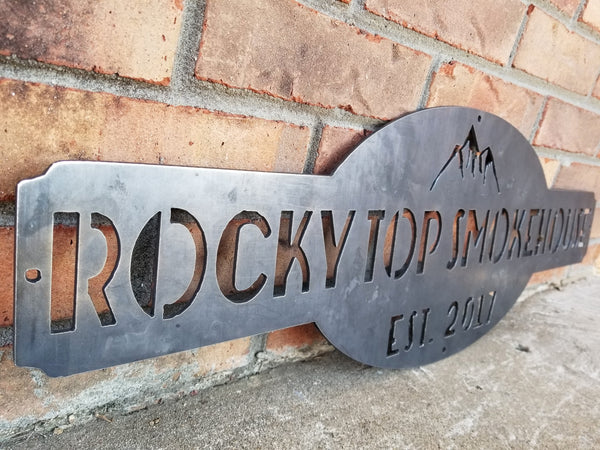 "This is a raw steel, custom metal sign.  At the top of the sign is an image of mountains. There is two lines of text on this sign which reads, ""Rockytop Smokehouse, Est. 2017"""