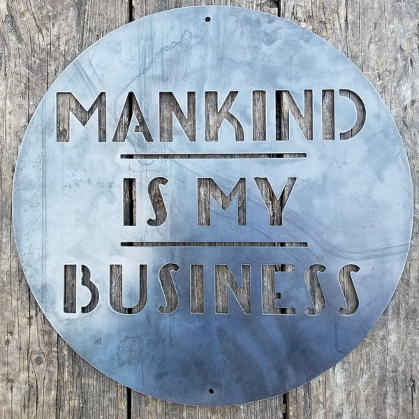 "This is a round art deco sign that has three lines of text with a straight line seperating them. The sign reads, ""Mankind Is My Business"""
