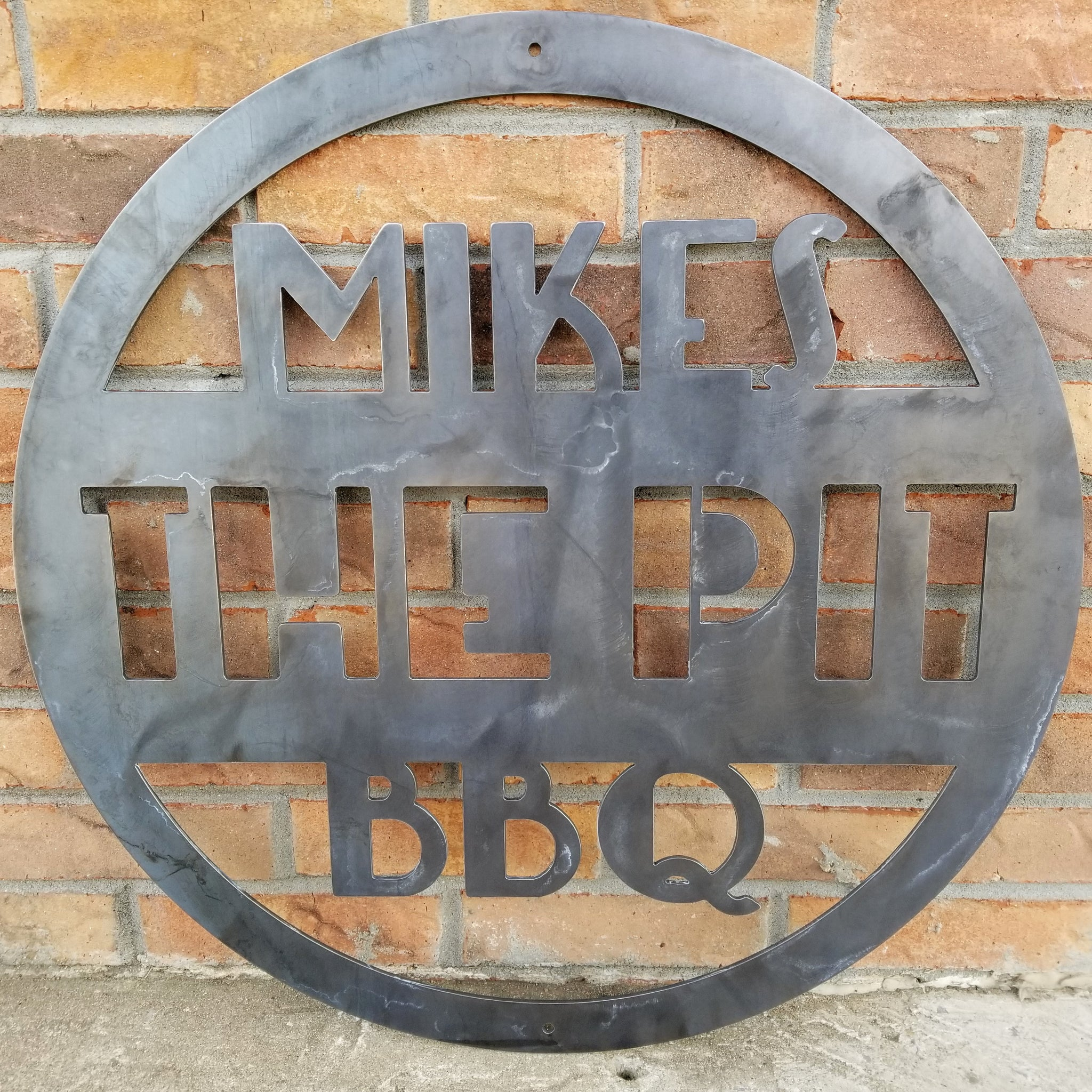 "This is a round art deco. sign that has three lines of text. The sign reads, "" Mikes The Pit BBQ"""