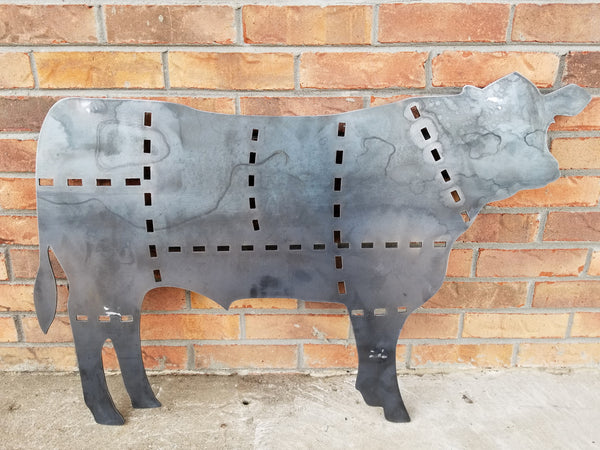 This is a metal sign in the shape of a cow with the cuts of beef outlined.