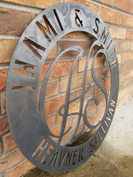 "Round raw steel monogram with two lines of text and two letters in the center. The sign reads, "" Jhami & Smith, Heavner-Sullivan"""
