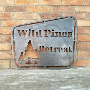 "This sign has a vintage design and depicts a group of trees. It reads, ""Wild Pines Retreat""."