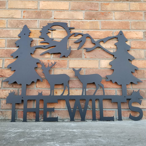 "A tree scene with a family of deer and the sun in the background. Underneath the scene the metal sign reads, ""The Wilts"""
